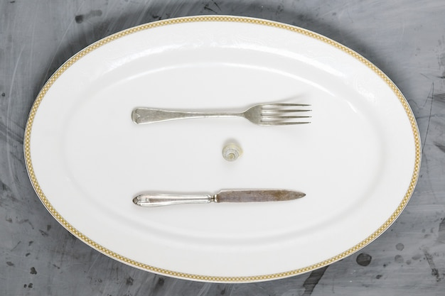 Snail, fork and knife on white plate on grey concrete background. copy space.