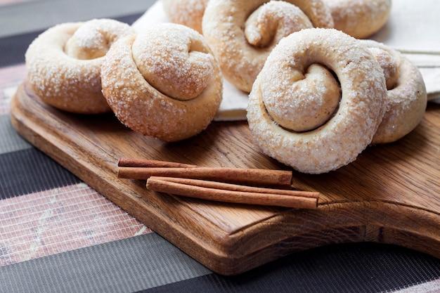 나무 보드에 계피와 달팽이 설탕 쿠키