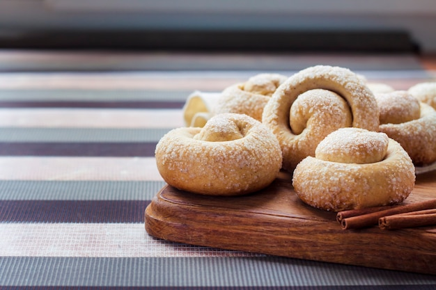 Snail sugar cookies with cinnamon on wooden board