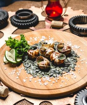 Улитки на деревянной доске тыквенные семечки лайм салат вид сбоку