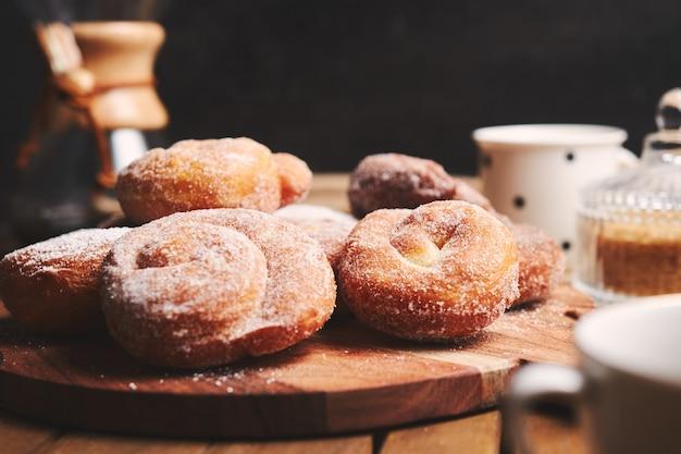 木製のテーブルに粉砂糖とchemexコーヒーとヘビドーナツ