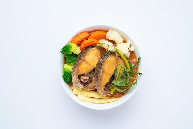 Змеиная голова в кислом супе из пасты из тамаринда с овощным омлетом - азиатский или тайский пищевой стиль изолированы