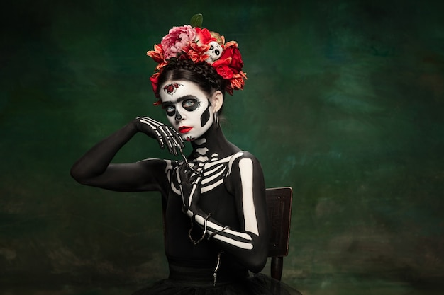 Snake queen. young girl like santa muerte saint death or sugar skull with bright make-up. portrait isolated on dark green studio background with copyspace. celebrating halloween or day of the dead.