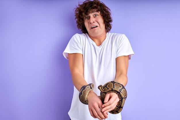 Змея связала руки человека крупным планом. парень стоит плачет от страха, думает, как освободиться от оков змеи