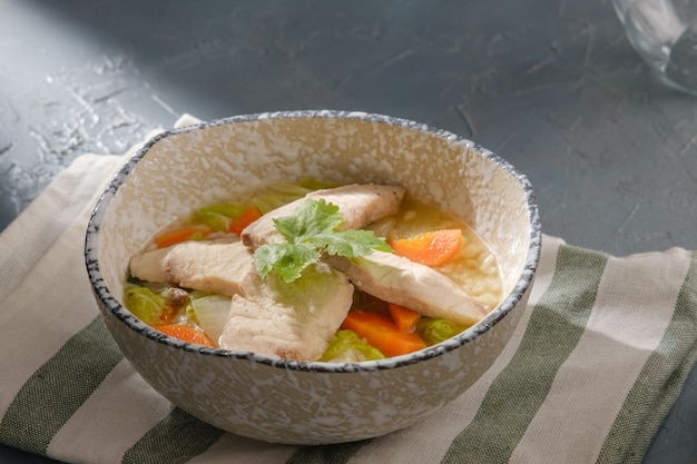 회색 테이블에 그릇에 고수를 얹은 snakehead 생선 죽. 얇게 썬 생선을 곁들인 쌀 수프. 죽 또는 콩지는 많은 아시아 국가에서 인기있는 죽 또는 죽의 일종입니다.