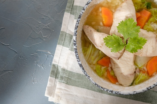 灰色のテーブルのボウルにコリアンダーをトッピングしたライギョのお粥。魚のスライスとご飯のスープ。