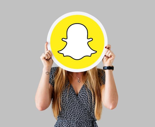 Snapchatアイコンを示す女性