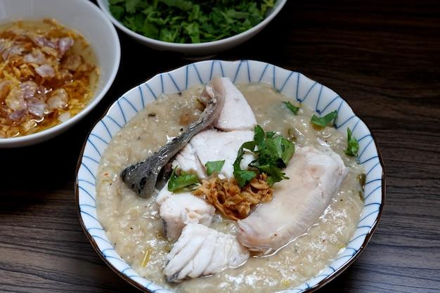 ボウルに鯛の魚のお粥と木製のテーブルにニンニクと油とコリアンダーを揚げた
