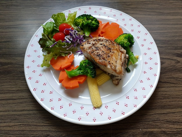 Snapper fish steak with broccoli carrot baby corn tomato lettuce red cabbage on a white plate