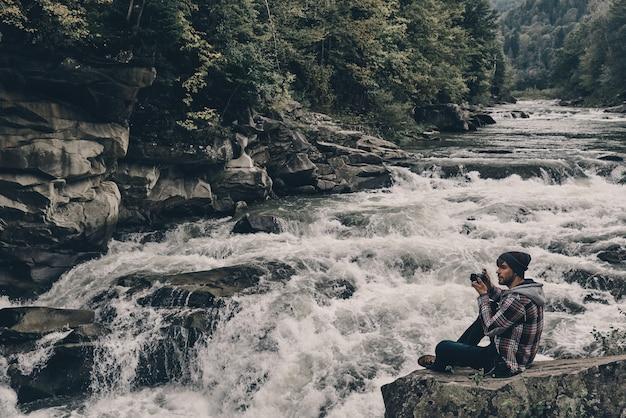 Снятие воспоминаний. красивый молодой современный человек фотографирует сидя на скале у реки
