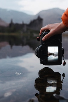 Snapping a shot of kilchurn castle reflected on loch awe, scotland