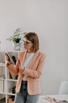 흰색 사무실에서 일하는 짧은 머리 여자의 snapportrait. 분홍색 재킷과 흰색 티셔츠를 입은 아가씨는 신중하게 태블릿으로 보입니다.