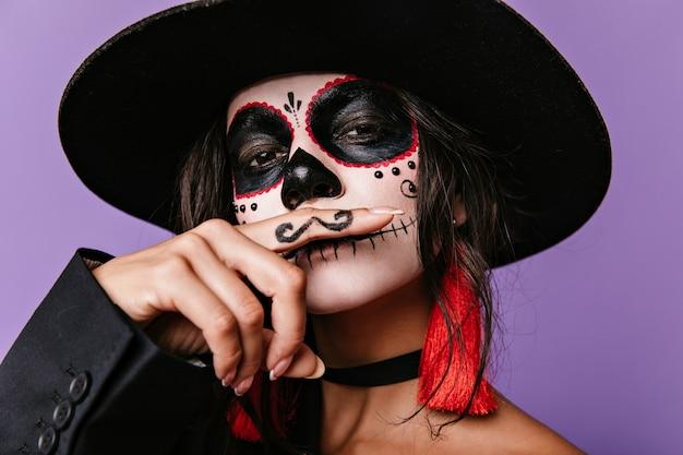Istantanea di una ragazza brillante con un cappello a tesa larga raffigurante un messicano con i baffi. signora dai capelli scuri in posa sulla parete lilla.