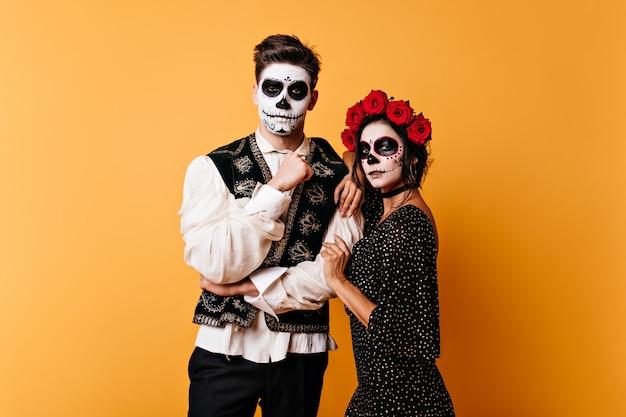Istantanea di coppia con arte del viso per il giorno dei morti. giovane donna con la corona di rose abbraccia il ragazzo dai capelli scuri.