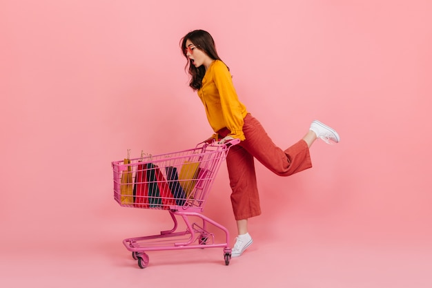 Snapshot full-length if girl shopaholic in bright outfit. model carries supermarket trolley with packages.