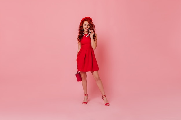 블루 아이드 여성 생강 코 케트의 전체 길이 스냅 샷. 미니멀 한 밝은 드레스, 베레모 및 빨간 가방. 하이힐을 착용하고 안경을 물고 분홍색 공간을 포즈를 취하는 여자.