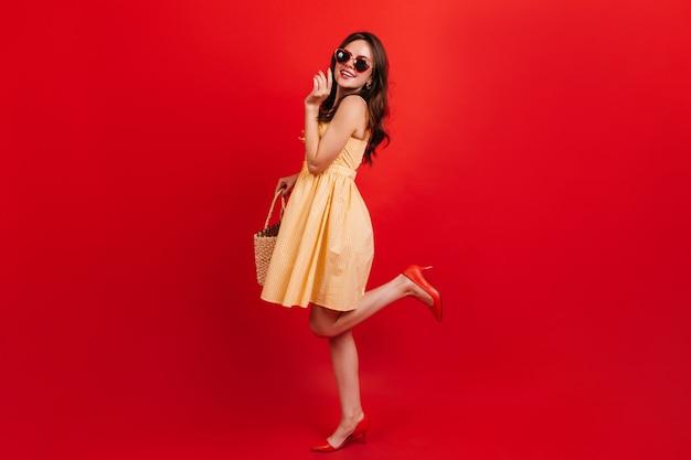 붉은 벽에 짧은 노란색 드레스에 예쁜 여자의 전체 길이 스냅 샷. 선글라스에 검은 물결 모양의 머리를 가진 여자는 귀여운 미소입니다.