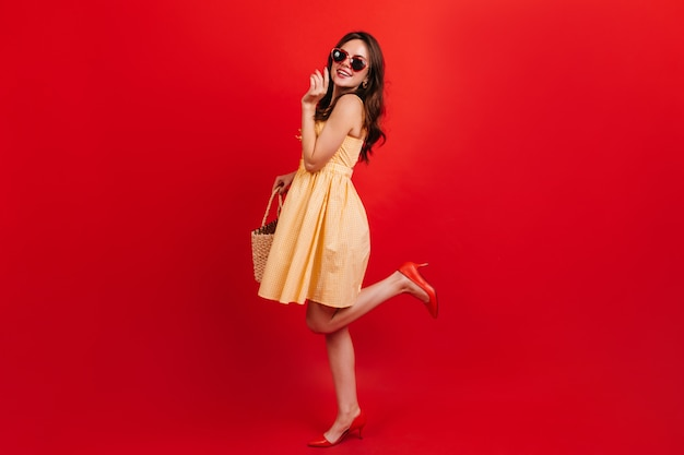 Snapshot full-length of pretty girl in short yellow dress on red wall. woman with dark wavy hair in sunglasses is smiling cute.