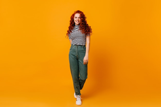 Snapshot of ginger woman in denim pants. girl in great mood moves on orange isolated space.