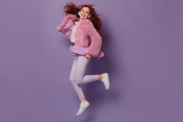ロングボードでジャンプする楽しい女の子の完全な成長のスナップショット。白いジーンズとピンクのコートでポーズをとる巻き毛の女性。