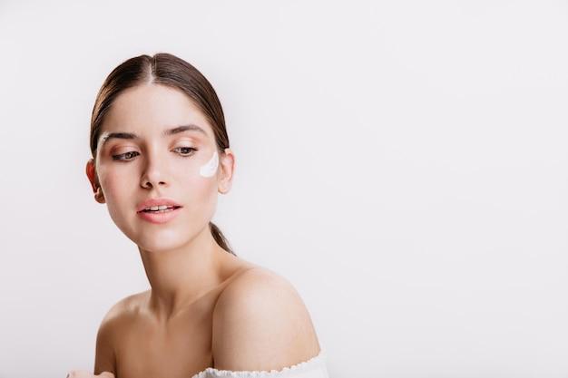 Снимок красивой темноволосой женщины с питательным кремом на лице.