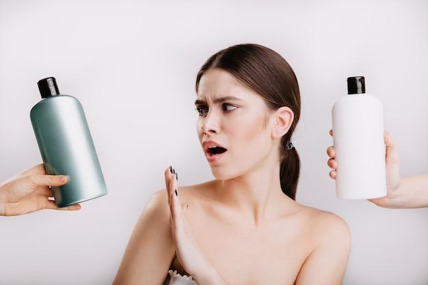 흰 벽에 아름다운 아가씨의 스냅 샷입니다. 소녀는 자연을 위해 화학 물질과 함께 샴푸 사용을 거부합니다.
