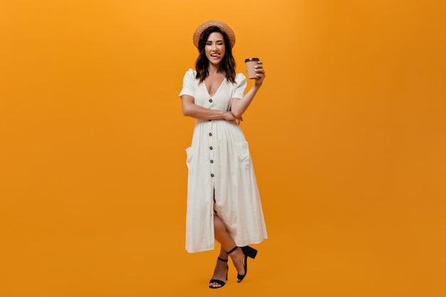 Снимок девушки в полный рост в платье миди с стаканом кофе