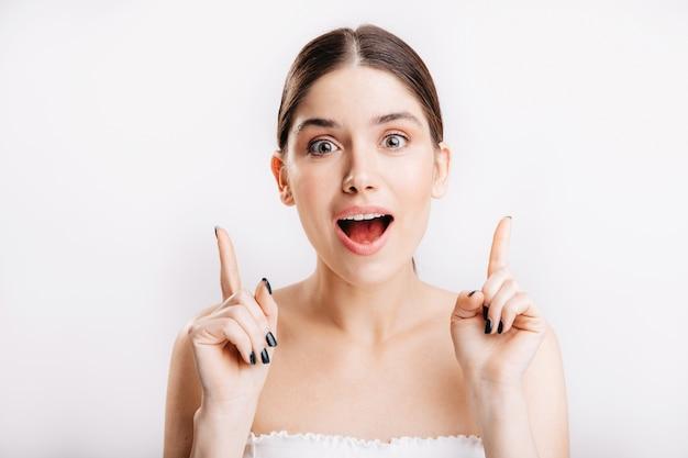 白い壁に化粧をしていない女の子のスナップショット。緑の目を持つブルネットはクールなアイデアを持っています。
