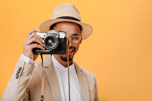 レトロなカメラを保持しているスタイリッシュな帽子とジャケットの男のスナップショット
