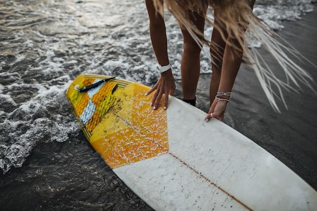 海の水にサーフボードを置く長髪の少女のスナップショット
