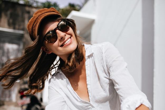 밖에 서 여름 화창한 날을 즐기는 여자의 스냅 샷. 유행 셔츠와 모자 웃는 소녀.