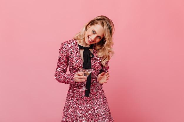 ピンクの壁にマティーニグラスでポーズをとって、元気いっぱいの女性のスナップショット