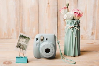 Snapshot picture; mini instant camera; bulldog paper clip and flower vase on wooden table