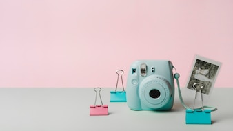 Snapshot picture with mini instant camera and bulldog paper clip against pink background