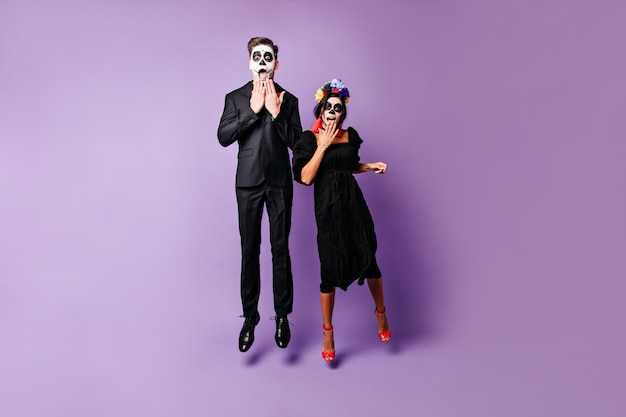 Snapshot of young slender guy and girl with painted faces in black outfits. couple from mexico looking surprised into camera, jumping on isolated background.