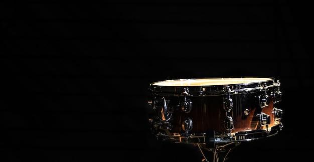 Tamburo rullante su sfondo nero, strumento a percussione al buio, spazio copia.