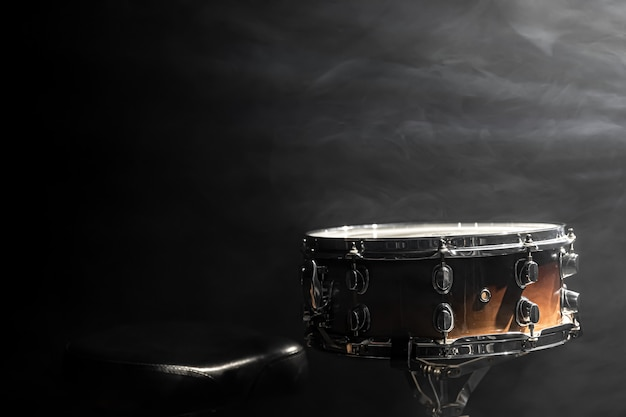 Snare drum on black background, percussion instrument in the dark with stage smoke, copy space.