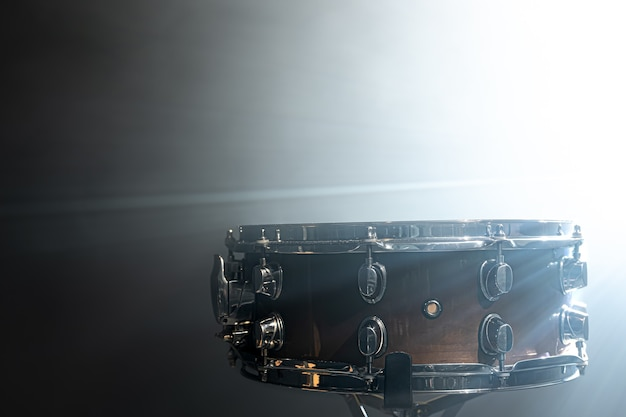 Snare drum, percussion instrument against the backdrop of a bright stage spotlight.