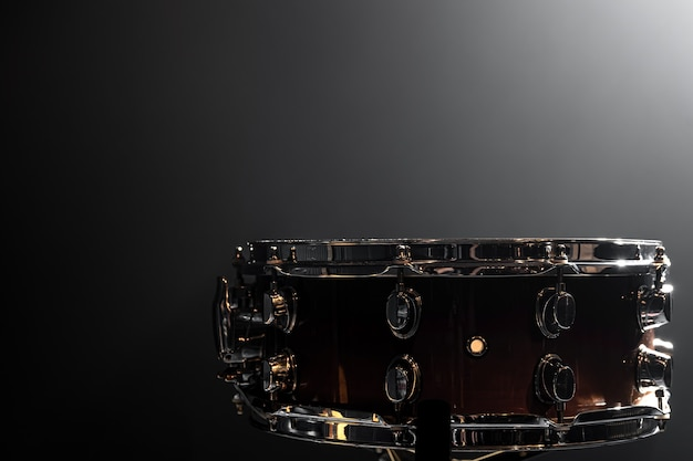 Snare drum, percussion instrument on a dark background with smoke, copy space.