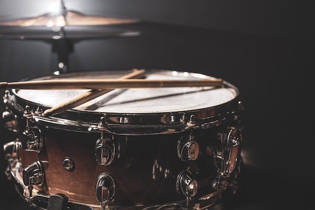 Snare drum, percussion instrument on a dark background with stage lighting.