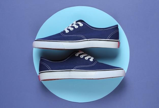 파란색 파스텔 원이 있는 보라색 배경 한가운데에 있는 운동화. 청소년 힙스터 개념입니다. 여름 재미. 평면도