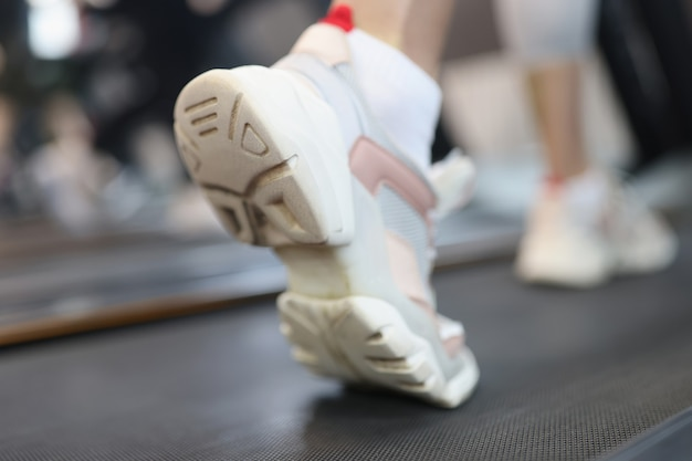 トレッドミルマシンで実行されているスポーツの女の子の運動のスニーカーの靴