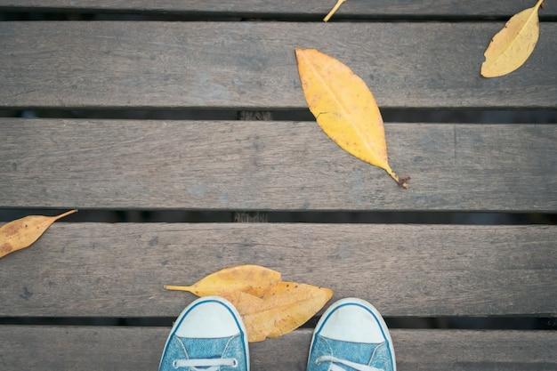 黄色の乾燥した葉を持つ木製の橋の上のスニーカーの靴。