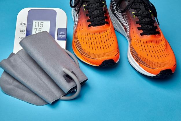 운동화와 혈압 모니터는 파란색 배경에 있습니다. 유산소 운동