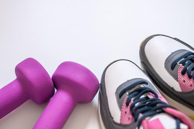 흰색 배경에 운동화와 아령 피트니스. 스포츠를위한 다른 도구. 개념 건강한 라이프 스타일, 스포츠 및 다이어트. 운동 장비. 공간을 복사하십시오. 피트니스 및 운동 액세서리의 평면 배치