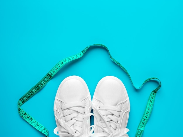 Sneakers are tied with measuring  on a blue background. the concept of an active lifestyle, the layout of the apartment. promotion of walking and a bonus weight loss. top view.