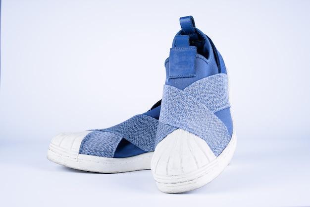 分離された白でペアになっている靴のようなスニーカーブルージーンズ