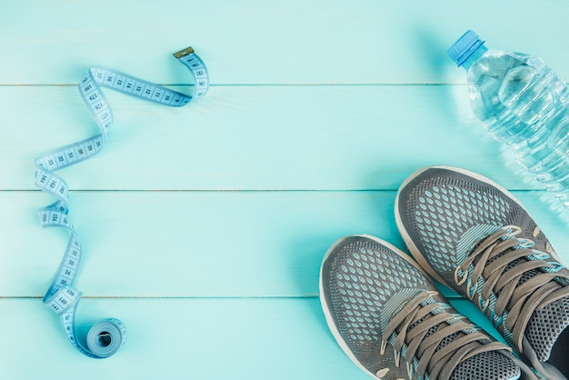 Sneakers, bottle of water and tape measure on blue, flat lay