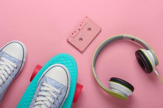 Sneakers on cruiser board, audio cassette, headphones on pink pastel surface