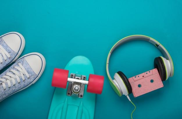운동화, 크루저 보드, 파란색 표면에 오디오 카세트가있는 스테레오 헤드폰